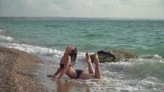 Kim Nadara does nude gymnastics by the sea